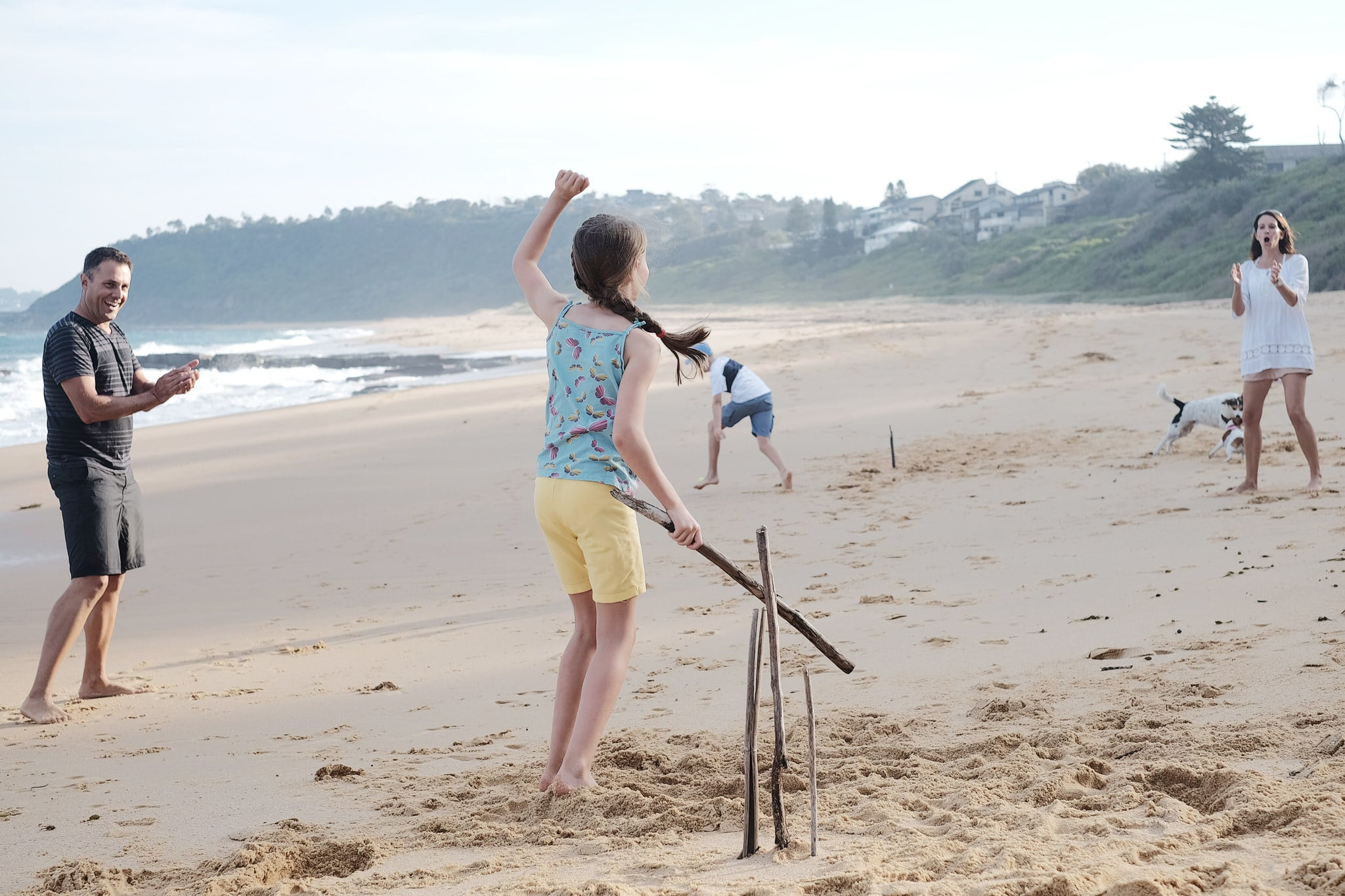 Family playing beach cricket