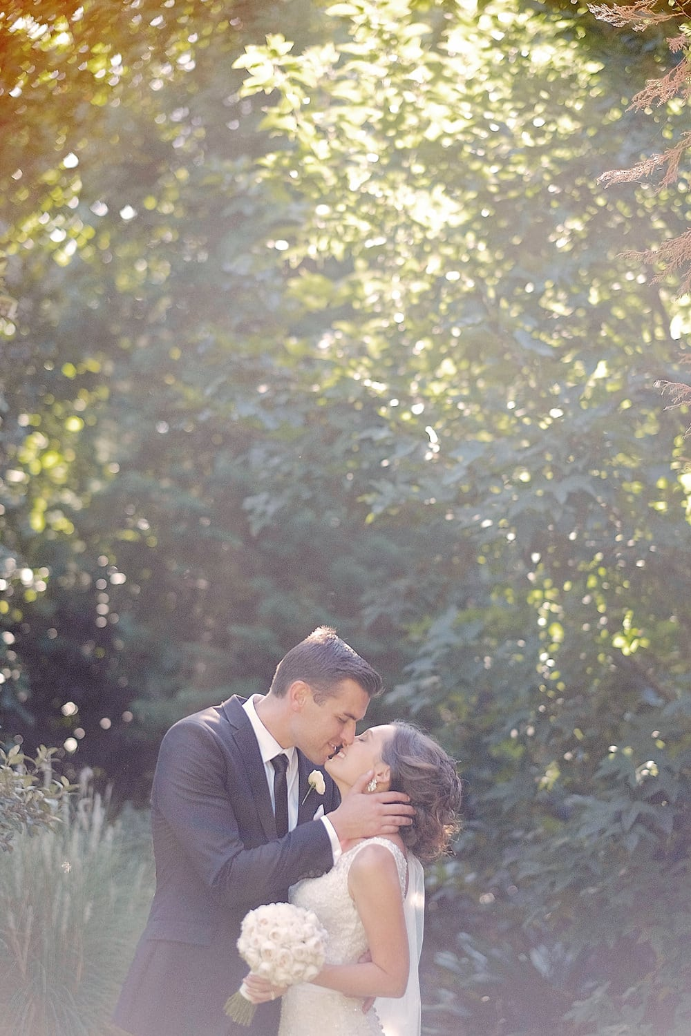 groom leaning over to kiss bride gently