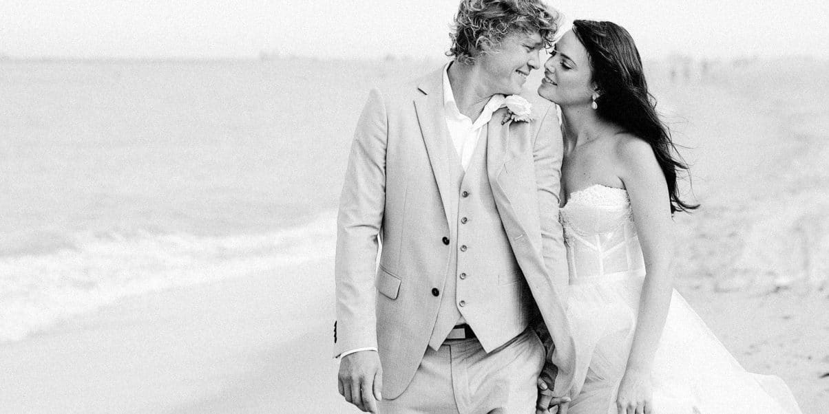 Just married gorgeous looking couple holding hands walking along Toowoon Bay beach looking into each others eyes