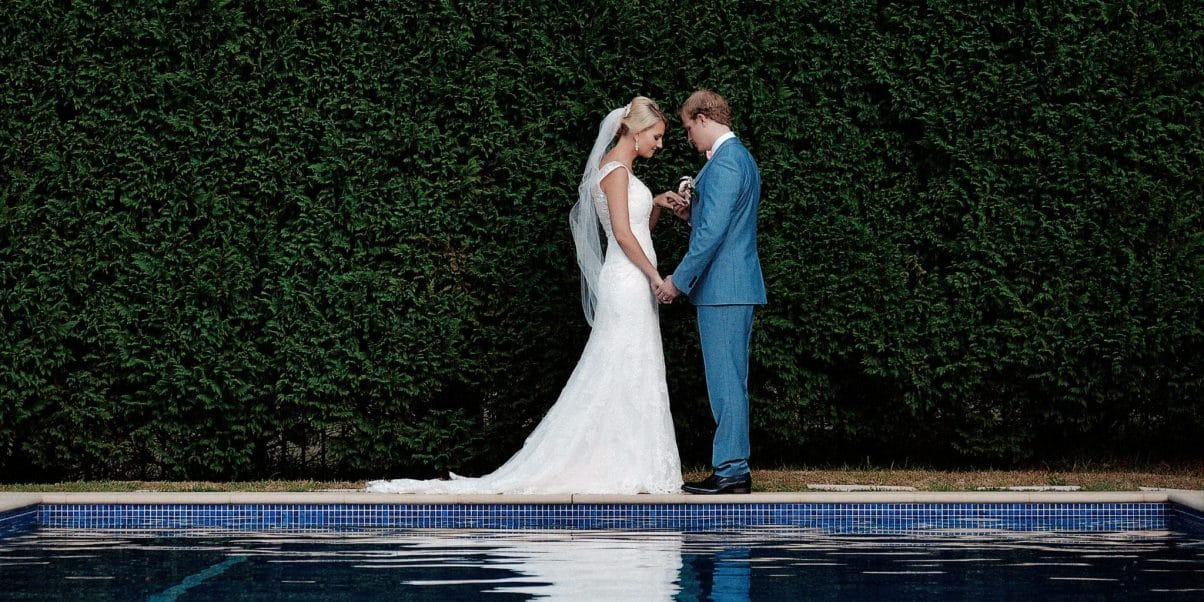 A groom inspects the wedding ring of his bride at the end of the Bells at Kildare pool on their wedding day