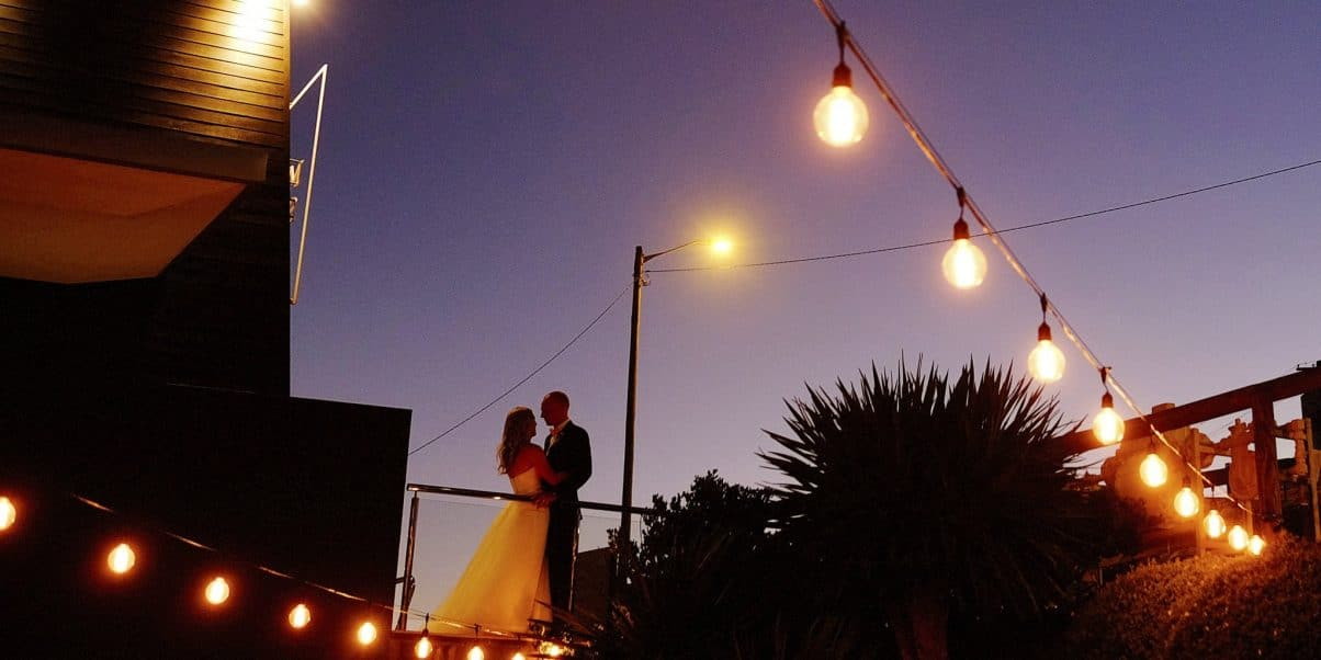 Newlyweds at Mereweather Surf House under the string lights at their wedding reception
