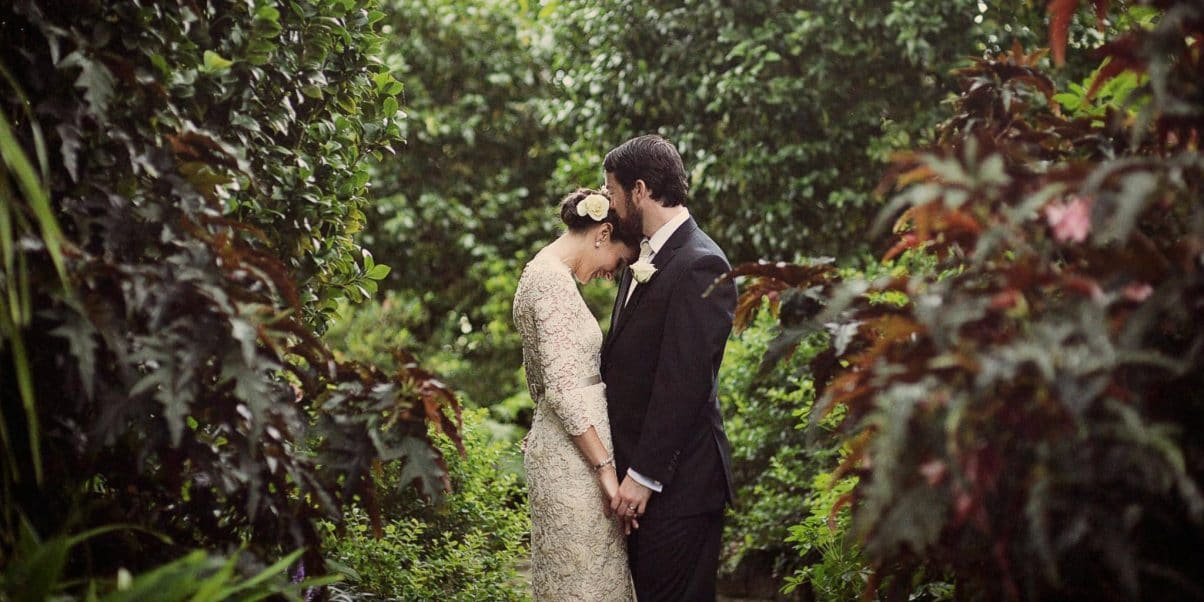 A bride affectionately drops her head into the shoulder of her groom on their wedding in the privacy of a hidden forrest on a golf course