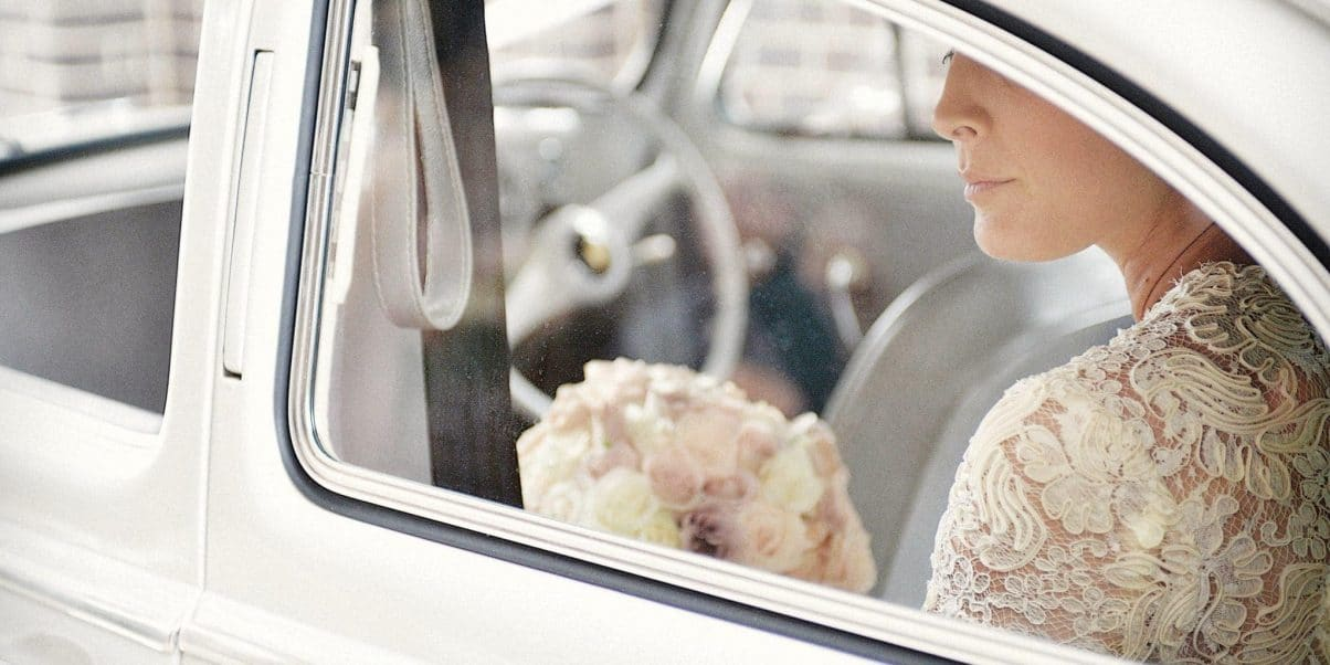 A bride on her wedding day in an amazing wedding gown looks from the wedding car window before heading out to her ceremony
