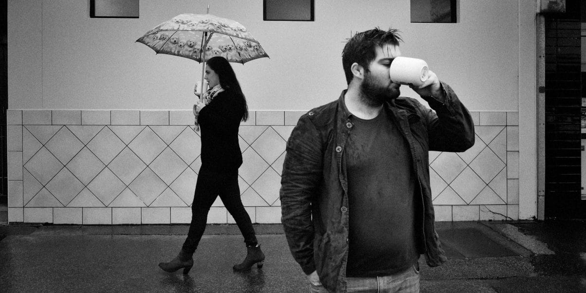 An engagement shoot photo at Umina on the Central Coast in the rain with the bride to be walking past with coffee cup and umbrella while the groom drinks from his cup in the rain